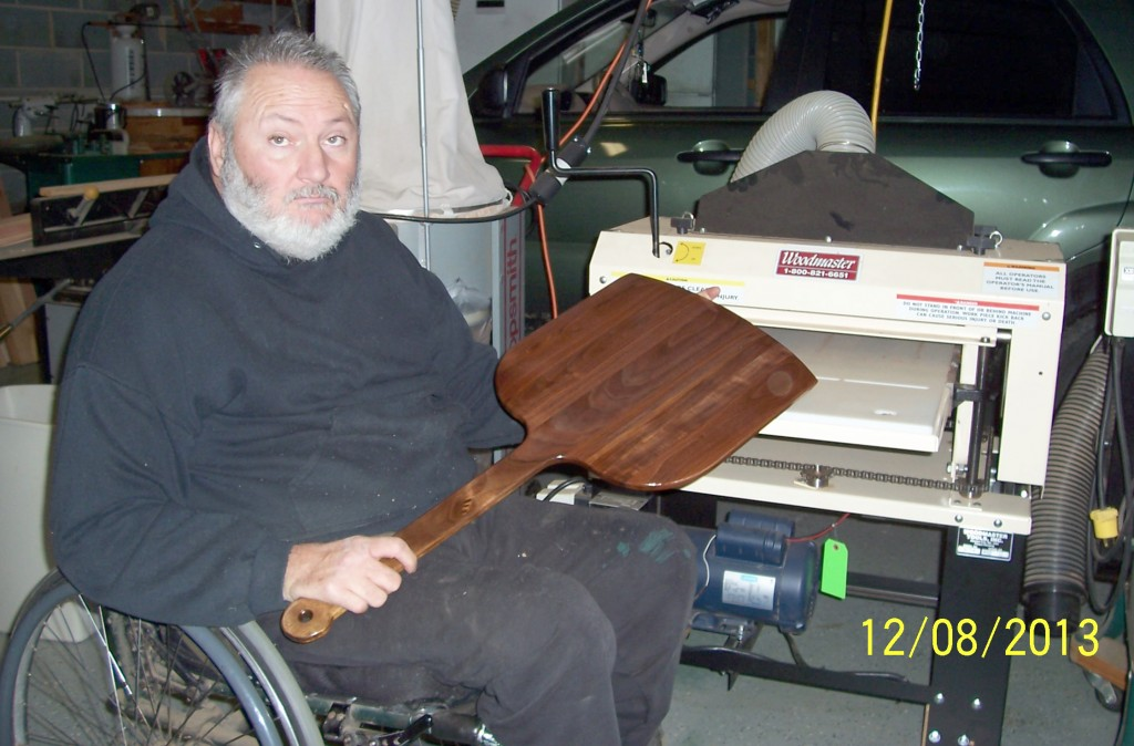 Johnny Starnes, of Tennessee, is an accomplished woodworker. He hasn't let disability slow him down -- here he is with his Woodmaster Molder/Planer and a hardwood pizza peel he's made.