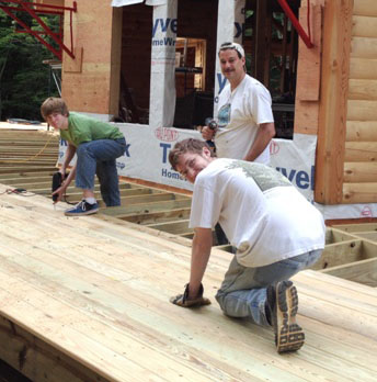 Eric and his two sons, Justin and Jordan, install decking on the home they built from scratch.