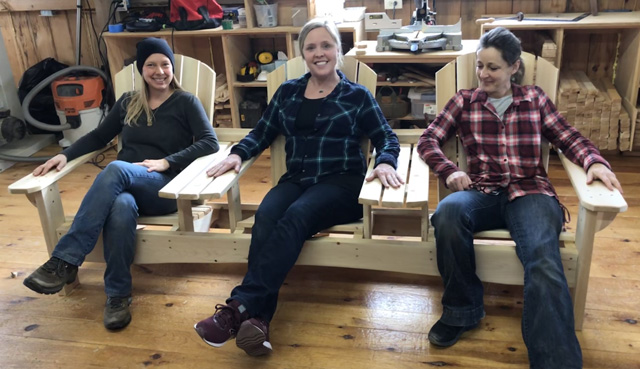 "Melissa (left) and Petra (right) run the shop at Maine Adirondack chairs. Ashley (center) is the host on ""Maine Cabin Masters."" Here they take a break after Melissa and Petra completed the 3-seat settee on-camera."