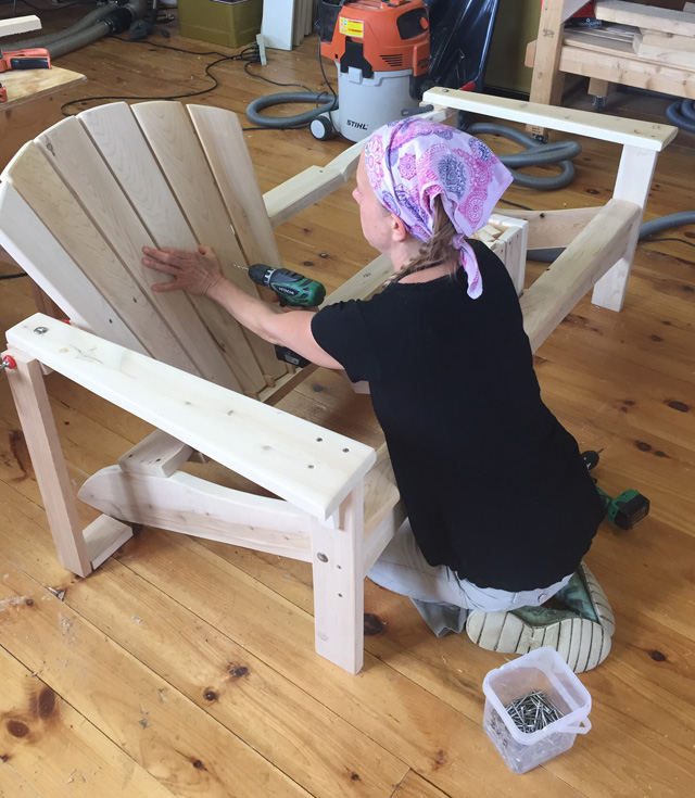 Rob's business started to take off to the point that he needed another pair of hands. Along came Melissa, shown here putting finishing touches on one of their handsome white cedar Adirondack chairs.