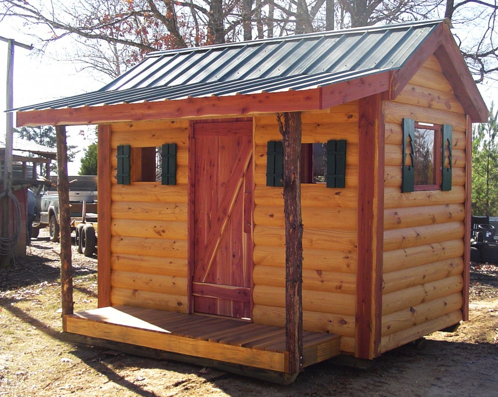 """The Patrick family makes log cabin siding with their Woodmaster Molder/Planer. This """"kid's cabin"""" is a display unit they built to show the quality of their siding. The cabin gets people's attention and helps the Patricks sell log cabin siding."""