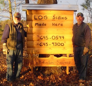 It pays to advertise. Steve (right) and his dad, Bill, set up a clever display on the road by their property. Passers-by can't miss it!