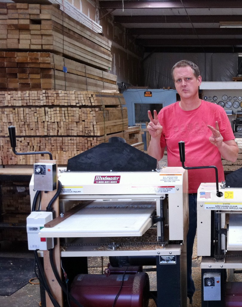 """Bill and Andy do some serious production with their Woodmasters. Behind Andy are stacks of stakes they manufacture, stacked and ready to go. Andy hand signal says, """"This is the second of our three Woodmasters."""""""