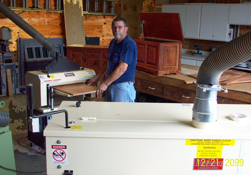 """Here's Charles in his workshop, running a panel through his Woodmaster Molder/Planer while his Woodmaster Drum Sander stands ready (foreground). Behind Charles are two of the toy boxes he's made for his grandkids. He has his work cut out for him: when we spoke, he had 13 grandkids, """"And one on the way!"""""""