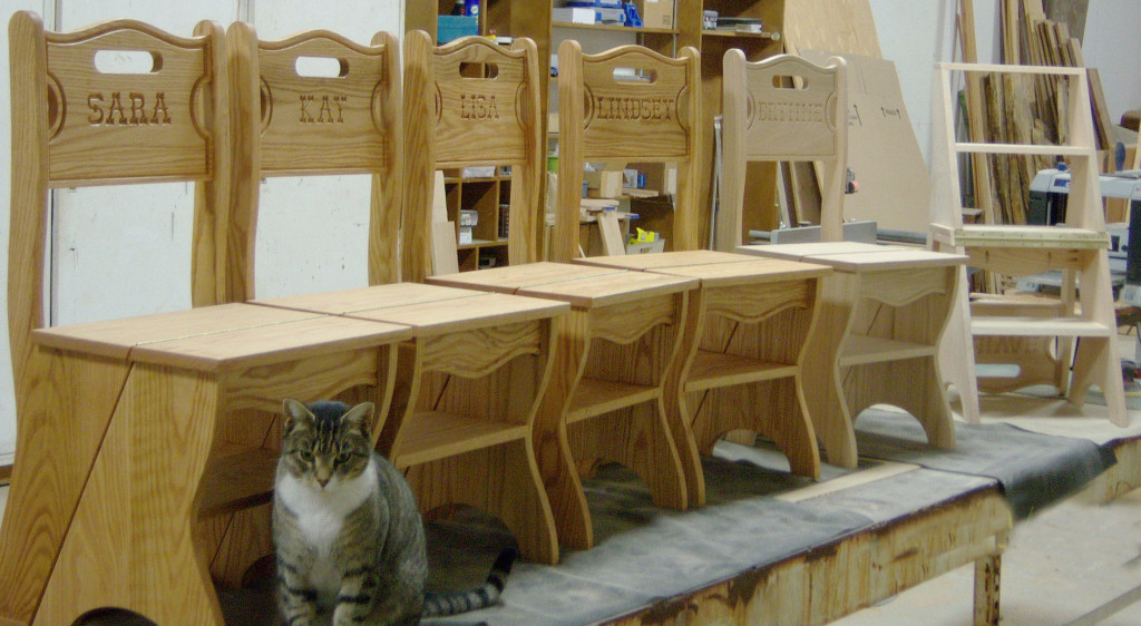"""Here's another family-oriented project by Mr. Hellewell. Dale's handsome """"Franklin Chairs"""" are each laser-engraved with the name of the soon-to-be recipient. The front of each chair lifts and hinges back to form a handy step stool -- see the example at far right in the photo."""