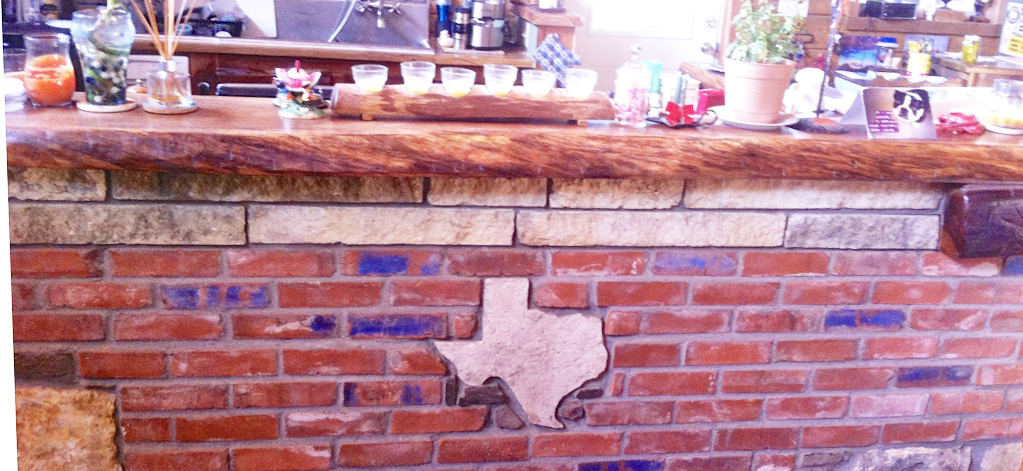 TJ displays his masonry and woodworking skills in this kitchen island. The thick live edge countertop sets off the brickwork nicely. And you can't beat the one-of-a-kind stone map of Texas!